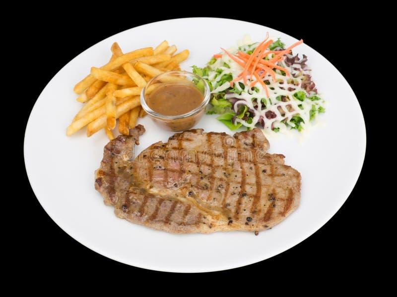 Provea de costillas el filete del ojo servido con las patatas fritas y las ensaladas a las verduras aisladas en el fondo negro co imagen de archivo