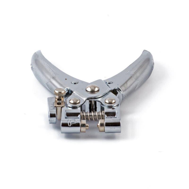 Proveja o alicate para o perfurador e os ilhós isolados no fundo branco imagem de stock