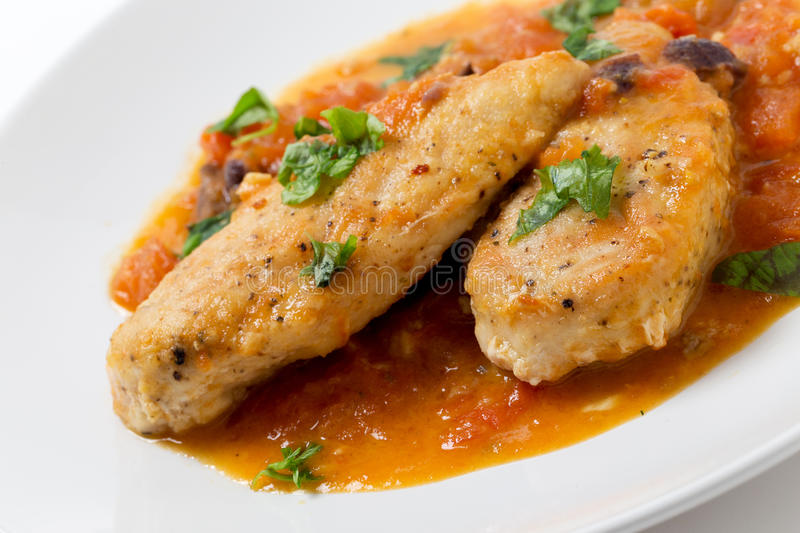 Provencal chicken breasts angled. Provencal chicken breasts, a simple French classic of floured fried chicken and a tomato, garlic, anchovy, wine and herbs stock images