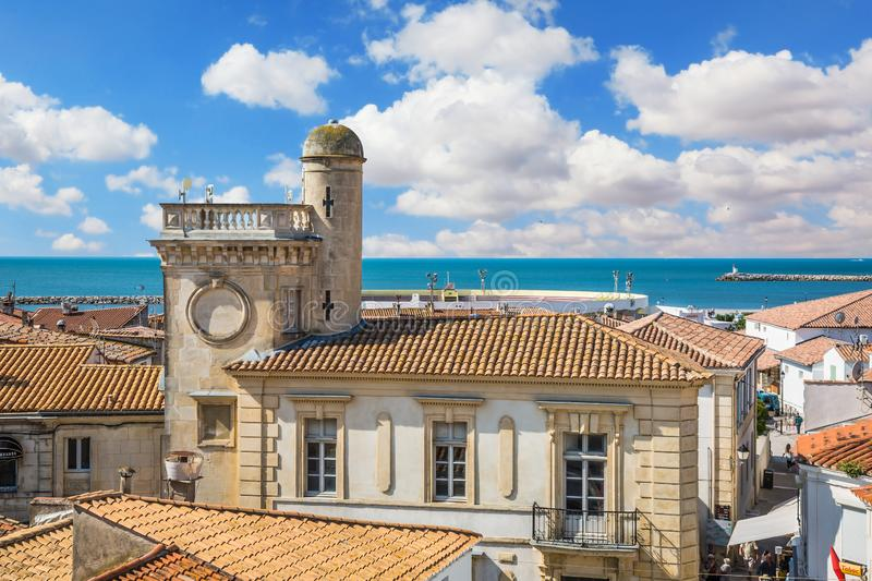 Provencal city on Mediterranean Sea. Sunny spring day in Saintes-Maries-de-la-Mer, Provence. Orange and yellow tiled roofs of Provencal city on Mediterranean Sea royalty free stock images