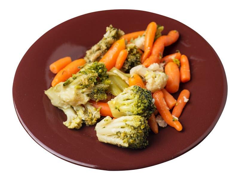 Provencal grönsaker på en platta grillade grönsaker på en platta som isoleras på vit bakgrund broccoli och morötter på en plattaö arkivfoto