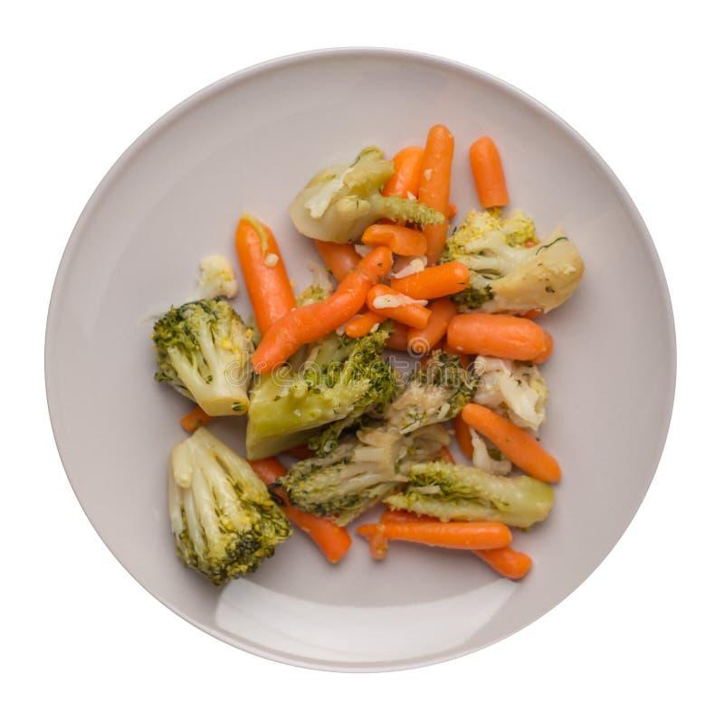 Provencal grönsaker på en platta grillade grönsaker på en platta som isoleras på vit bakgrund broccoli och morötter på en plattaö royaltyfria foton