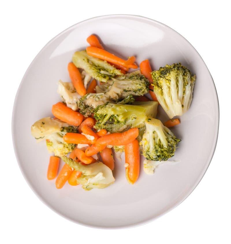 Provencal grönsaker på en platta grillade grönsaker på en platta som isoleras på vit bakgrund broccoli och morötter på en plattaö arkivbilder