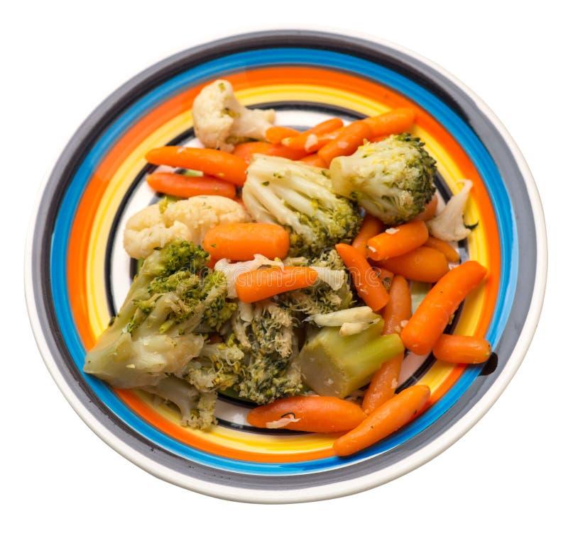 Provencal grönsaker på en platta grillade grönsaker på en platta som isoleras på vit bakgrund broccoli och morötter på en plattaö royaltyfria bilder