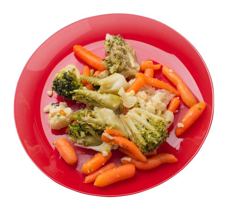 Provencal grönsaker på en platta grillade grönsaker på en platta som isoleras på vit bakgrund broccoli och morötter på en plattaö arkivbild