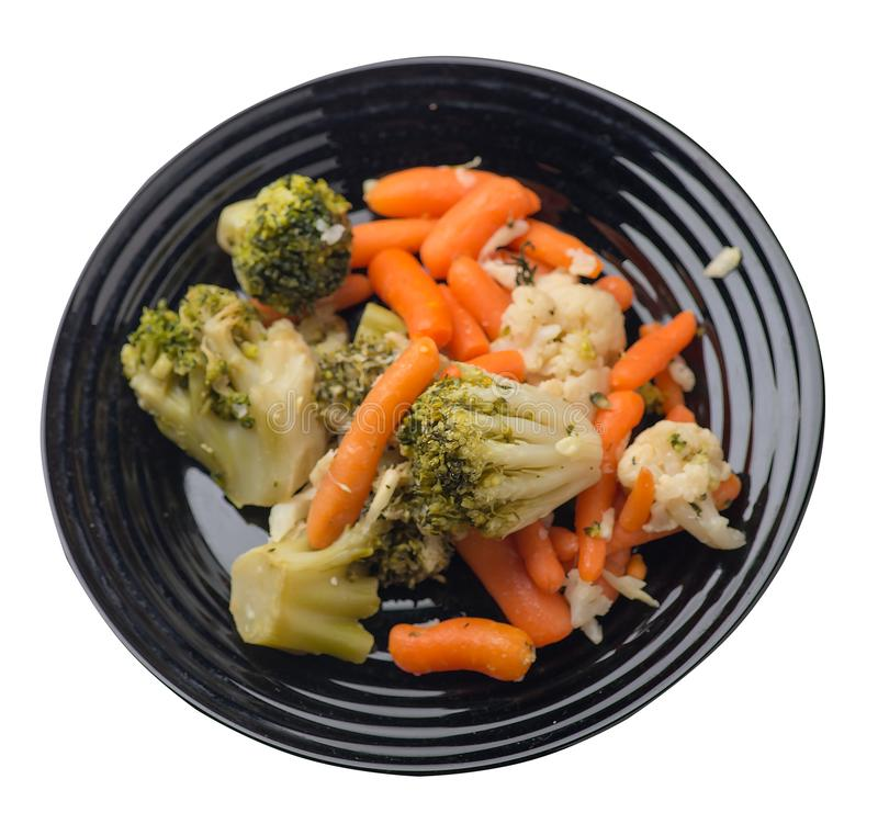 Provencal vegetables on a plate.grilled vegetables on a plate isolated on white background.broccoli and carrots on a plate top. Provencal vegetables on a black stock image