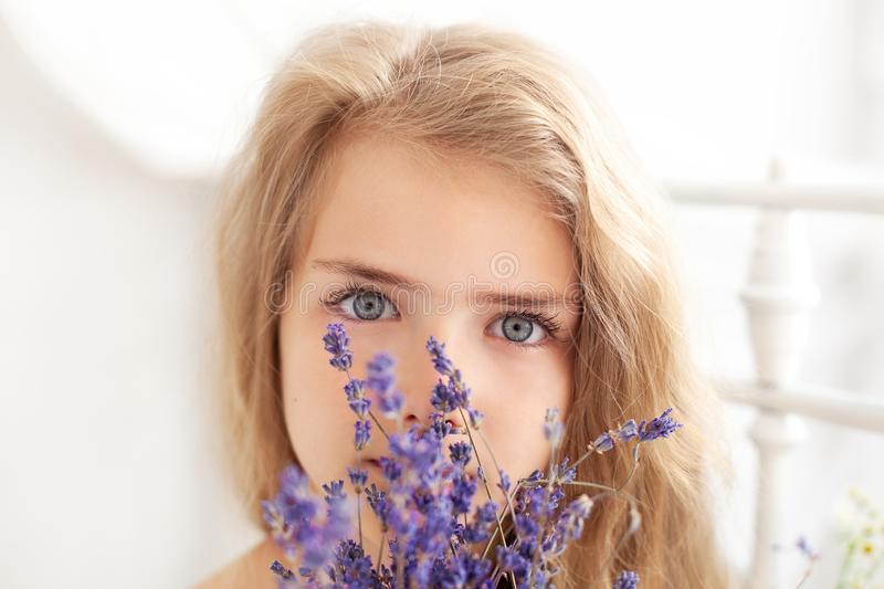 Provence. Portrait of a pensive blonde little girl holding a fragrant bouquet of lavender. The concept of childhood and beauty. Be royalty free stock photos