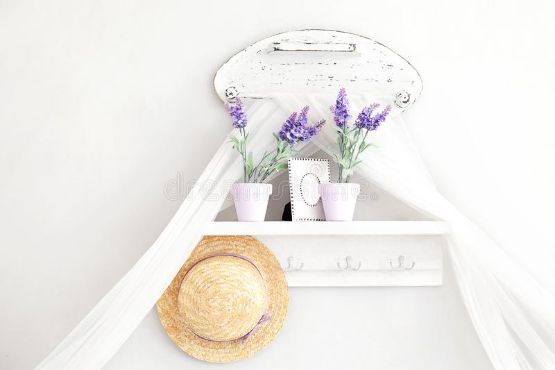 Provence, rustic style. Shabby chic in Provencal style. Village, country house. Shelf for hats, household trifles in a gentle Fren. Ch style on a white stock image