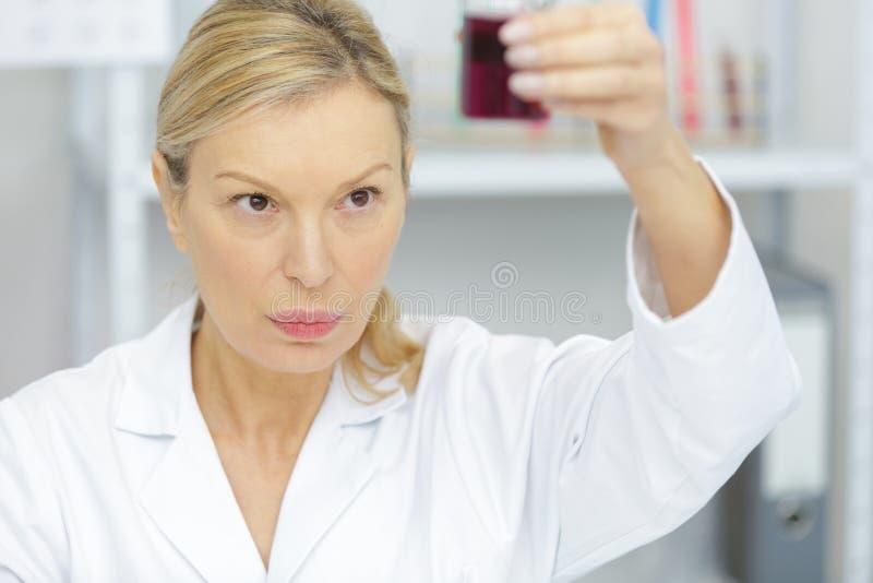 Provetta della tenuta della donna con il primo piano del campione di sangue immagine stock libera da diritti