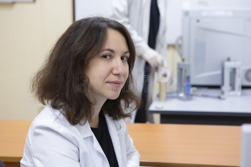 Provetta femminile di Examining Sample In dello scienziato del laboratorio fotografia stock