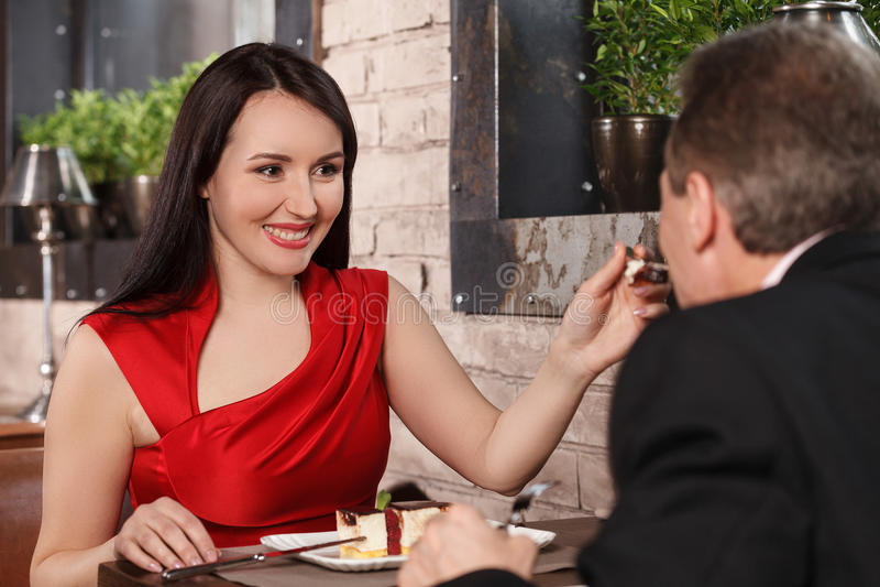 Provi questo dolce! Belle donne mature in vestito rosso che alimenta la sua b immagine stock