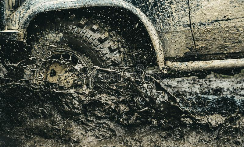 Provide the best experience for the offroader. Car racing offroad. Car wheels on steppe terrain splashing with dirt. Offroad car in action. Dirty car drive on stock photography