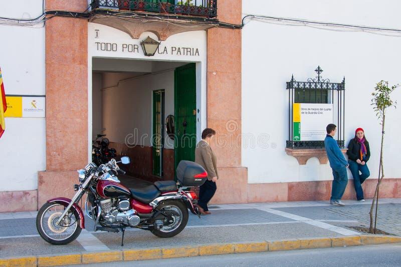 Province d'Olvera, Cadix, Andalousie, Espagne - 25 mars 2008 : deux garçons avec une moto devant le ` s de garde civile siège images stock