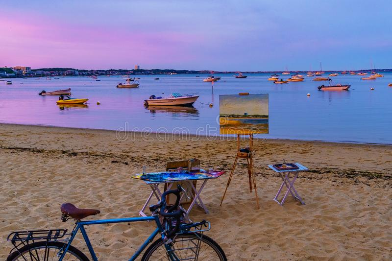 Provincetown, MA, USA - August 12 2017 Canvas, easel, bicycle, ships and boats in the Provincetown Marina during sunset.  royalty free stock image