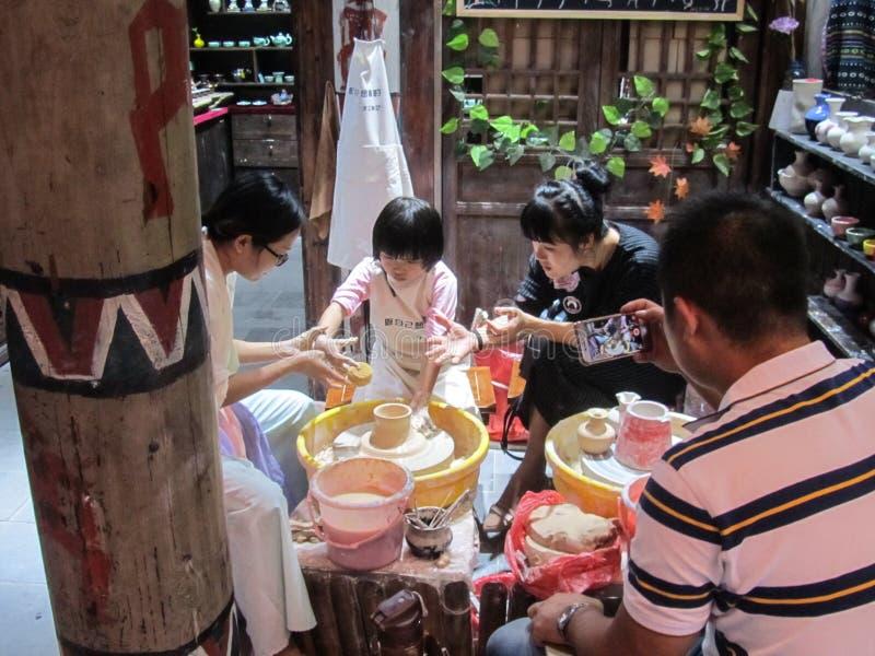 Provinz Chinas, Hainan, Sanya, am 21. Januar 2018 Ein Mädchen der asiatischen Nationalität lernt, die Teller auf a zu tun lizenzfreie stockfotos
