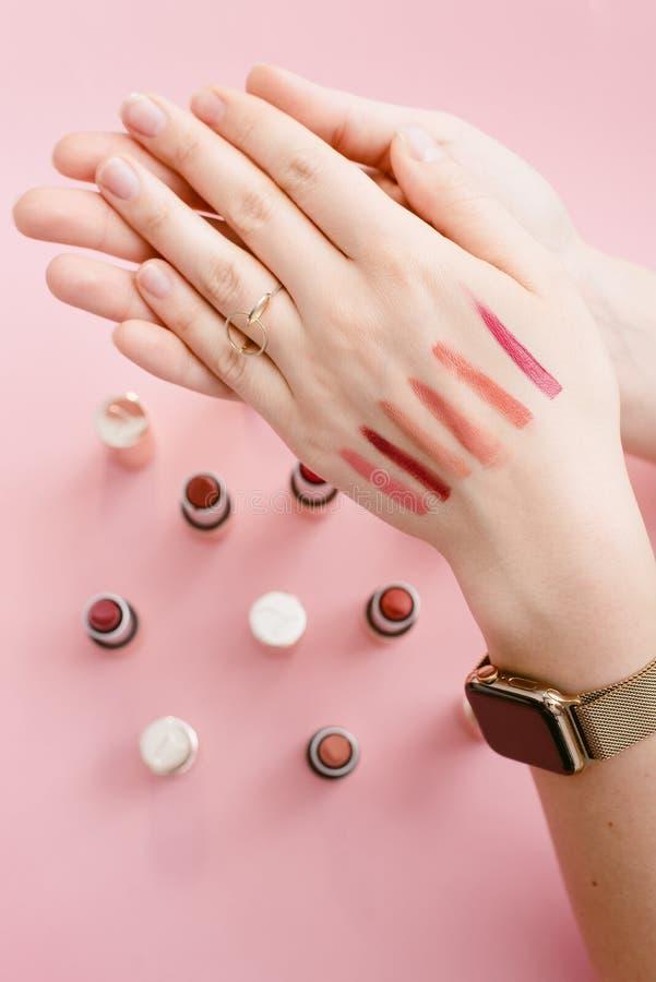 Provkartaläppstift på den tunna handen av en flicka Provkartor av olika läppstift på bakgrunden av läppstift på en pastellfärgad  royaltyfri foto