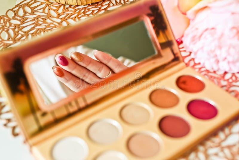 Provkartor av färgrika ögonskuggor på kvinnlina fingrar i reflexion av en palettspegel fotografering för bildbyråer