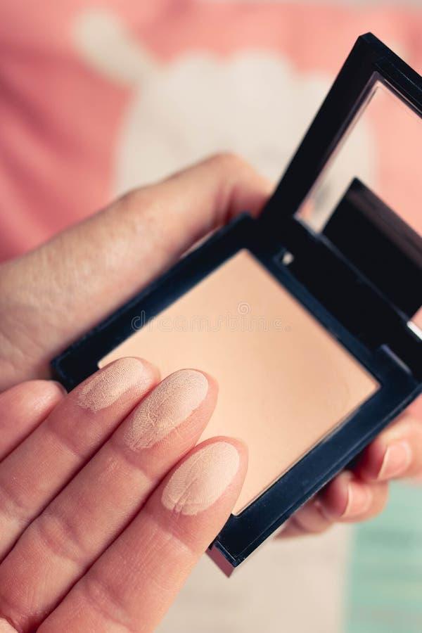 Provkartor för framsidapulver på kvinnliga fingrar och pulverpaletten bakgrund suddighetdde f?rgrikt arkivbild