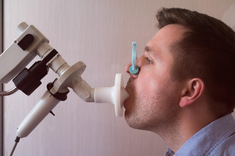 Provning för ung man som andas funktion vid spirometry arkivfoto