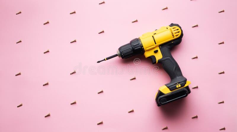 Provocação criativa: uma chave de fenda amarela em um fundo cor-de-rosa e em uns parafusos pequenos imagem de stock