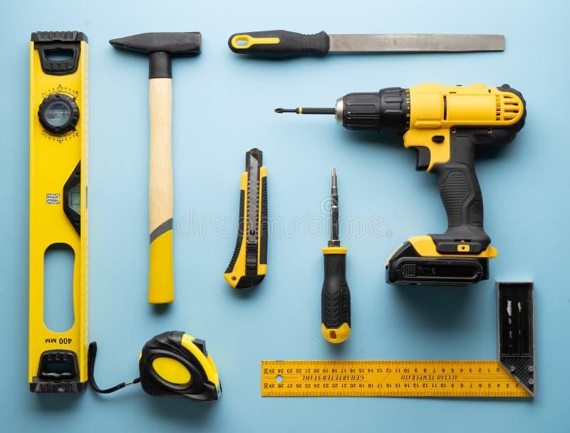 Provocación creativa: una disposición plana de las herramientas amarillas de la mano en un fondo azul fotos de archivo libres de regalías