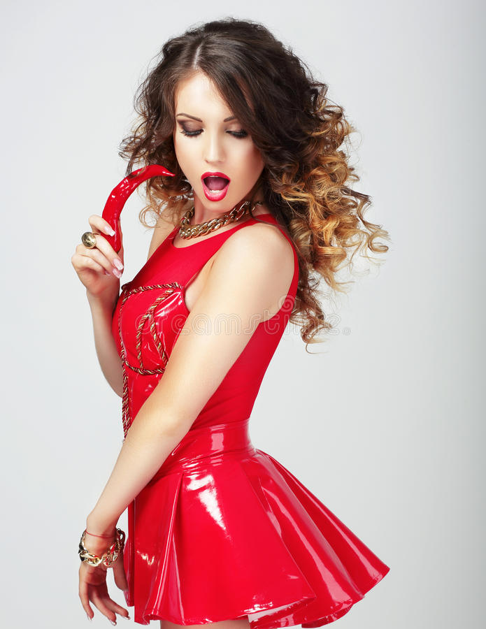 Provocative Female in Red Clothes with Hot Chili Pepper royalty free stock image