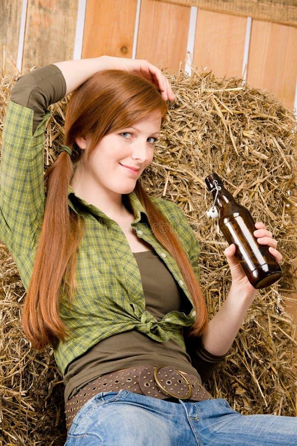 Provozierendes junges Cowgirlgetränkbier im Stall stockbild