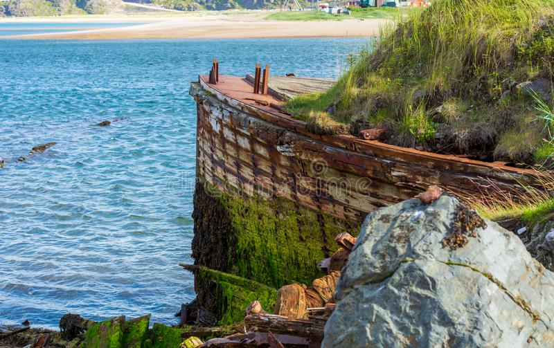 The prow of a big old ship. Overgrown with moss and bushes. Nature takes its toll, destroying what man has created. Nature absorbs the old wooden ship stock photos