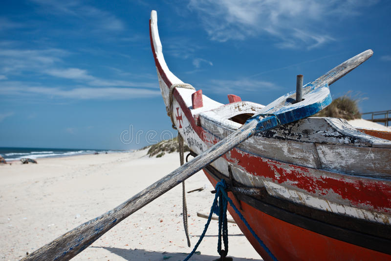 Prow of colorful old beached Portguese fishing boat with oar. Prow of colorful, old, weathered, Portuguese fishing moliceiros boat with an oar in oarlock sits on royalty free stock photography