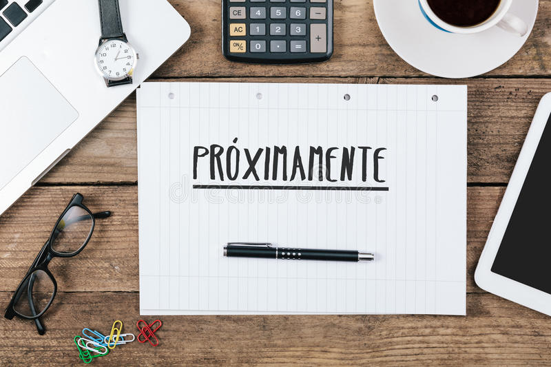 Proximamente, Spanish text for Coming Soon on note pad at office. Proximamente, Spanish text for Coming Soon, on note pad at office desk with electronic devices stock photo