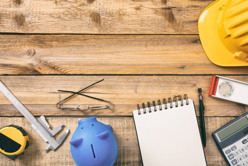 Proyecte la hucha del coste de construcción, la calculadora y el equipo en un escritorio de madera, espacio de la copia, visión s fotos de archivo libres de regalías
