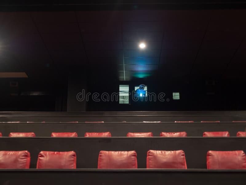 Proyector de película del cine que juega en un teatro vacío imagen de archivo