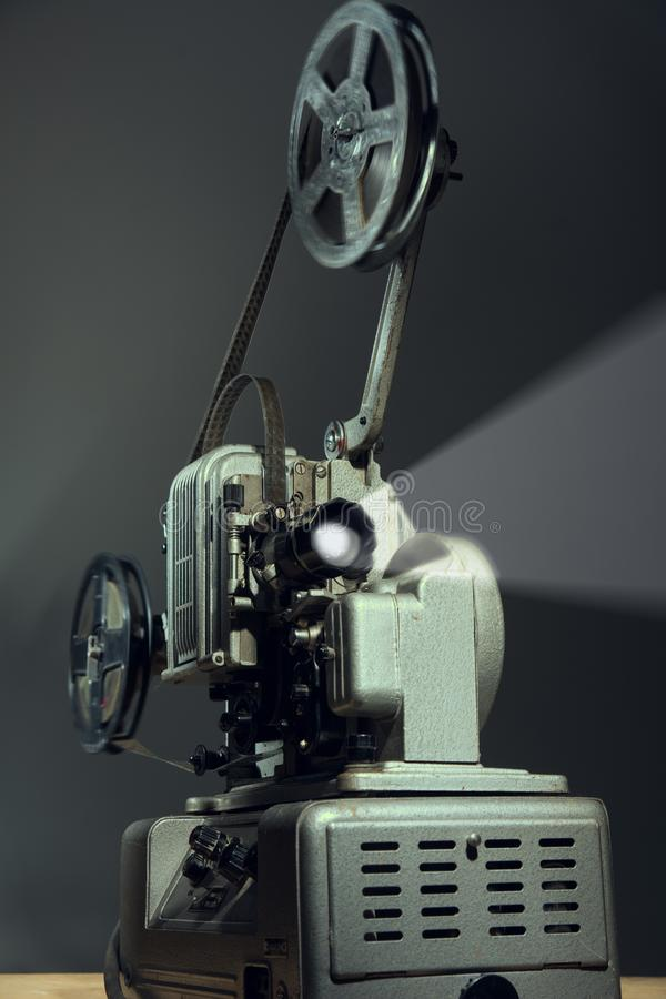Proyector del cine con una película en fondo oscuro imagenes de archivo