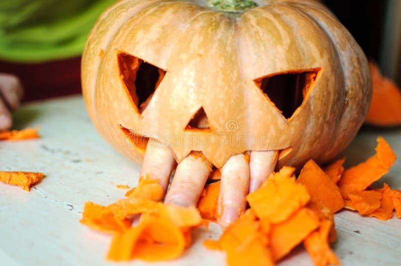 Prozess der Herstellung der Jack-O-Laterne Lustiges Bild des Halloween-Kürbismonstergesichtes mit den männlichen Fingern stockbild