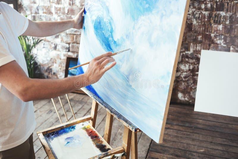 Prozess der Zeichnung mit oilpaints und Malerpinsel Künstlerfarben auf Segeltuchmalerei auf Gestell im Studio lizenzfreies stockbild