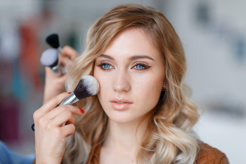 Prozess des Anwendens des Makes-up auf dem Mädchen ` s Gesicht stockbild