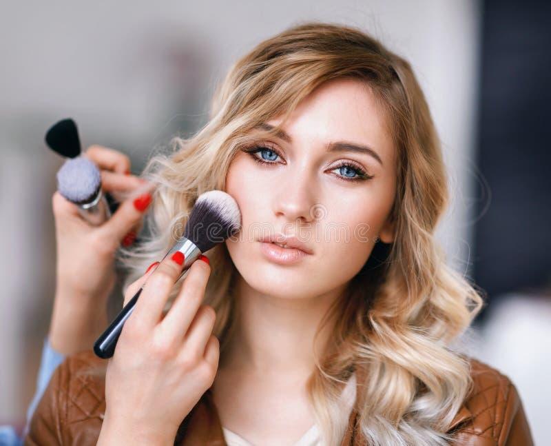 Prozess des Anwendens des Makes-up auf dem Mädchen ` s Gesicht lizenzfreies stockbild