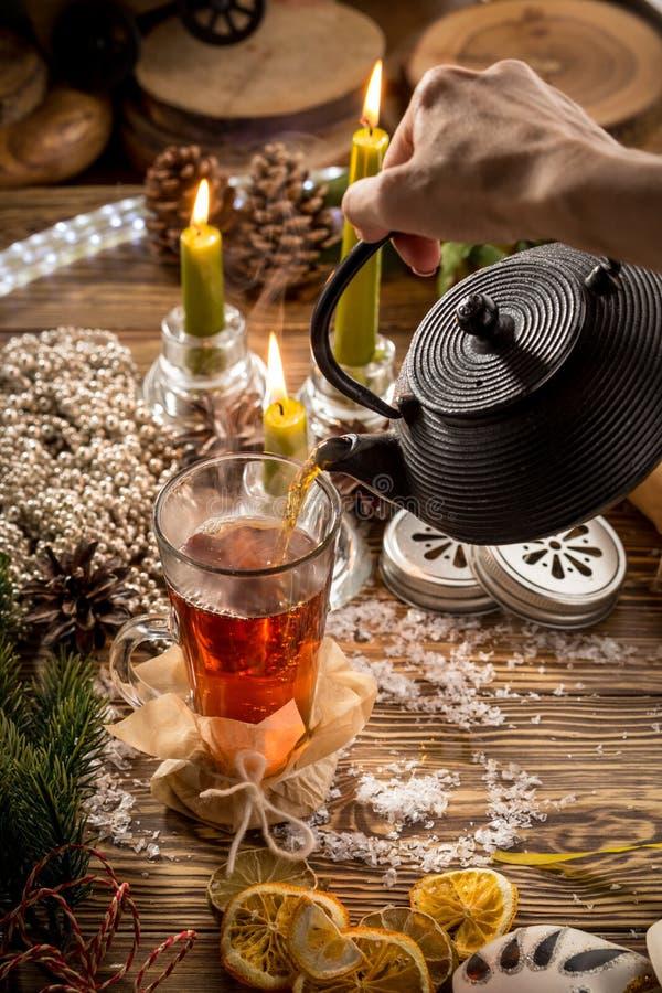 Prozess des Gießens des Tees in die Glasschale auf Holztisch auf Weihnachten verziertem Hintergrund lizenzfreie stockfotos