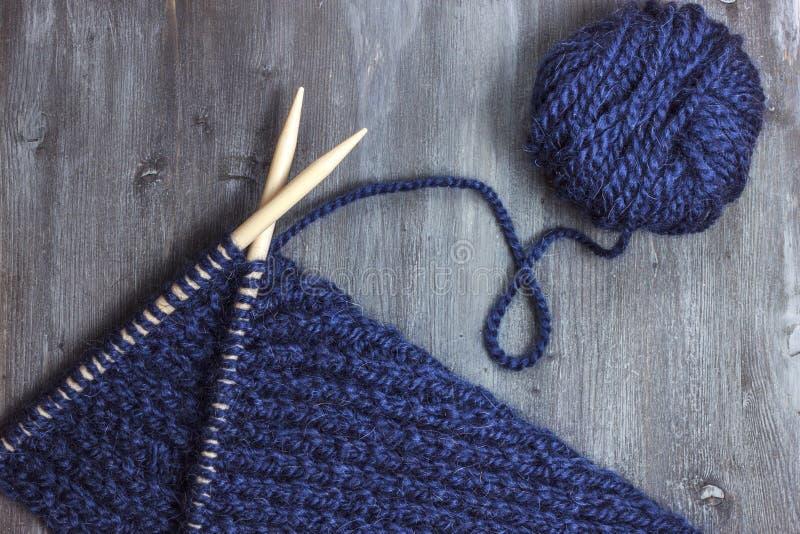 Prozess des Strickens Ball der blauen Garn- und Stricknadelnahaufnahme auf hölzernem lizenzfreies stockfoto
