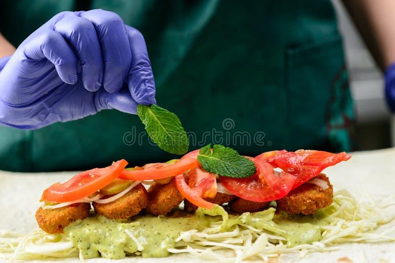 Prozess des Vorbereitens der appetitanregenden Rolle mit Falafel, Gemüse lizenzfreie stockfotografie