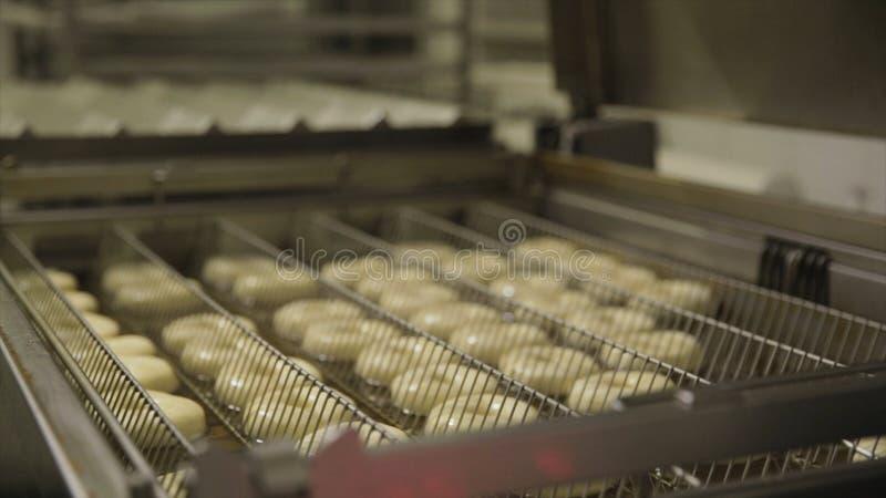 Prozess des Vorbereitens von Schaumgummiringen in Bratfett an der Fabrik, gebratenen an den Teigsüßigkeiten oder am Nachtischnahr stockfotografie