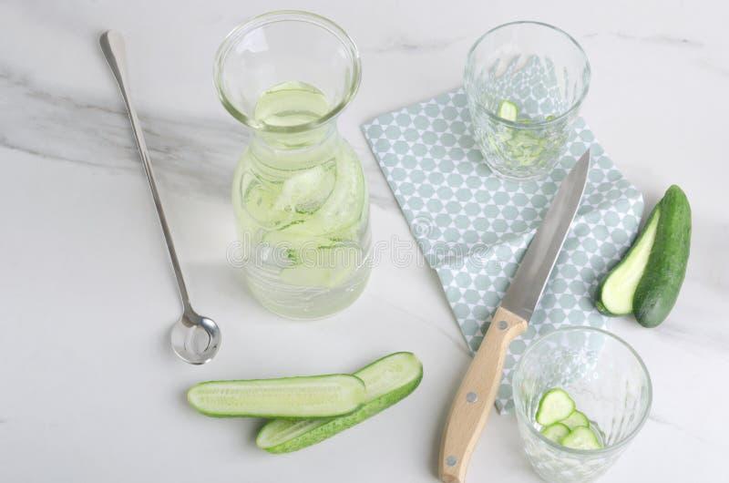 Prozess des Vorbereitens des Wassers mit Gurke, Auffrischungsgetränk lizenzfreies stockfoto