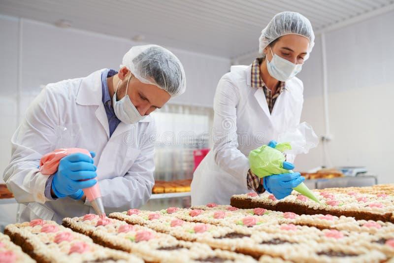 Prozess von den Kuchen, die auf Fabrik verzieren stockfotos
