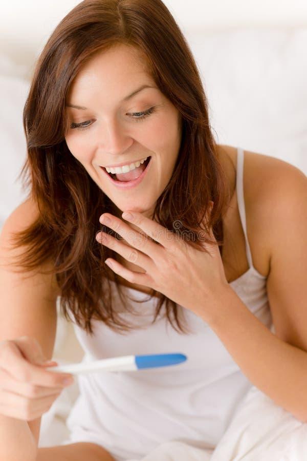 Prueba de embarazo - mujer sorprendida feliz imagenes de archivo