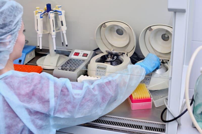 Prueba de la DNA en el laboratorio un técnico de laboratorio con un dispensador en sus manos está conduciendo análisis de la DNA  fotografía de archivo libre de regalías