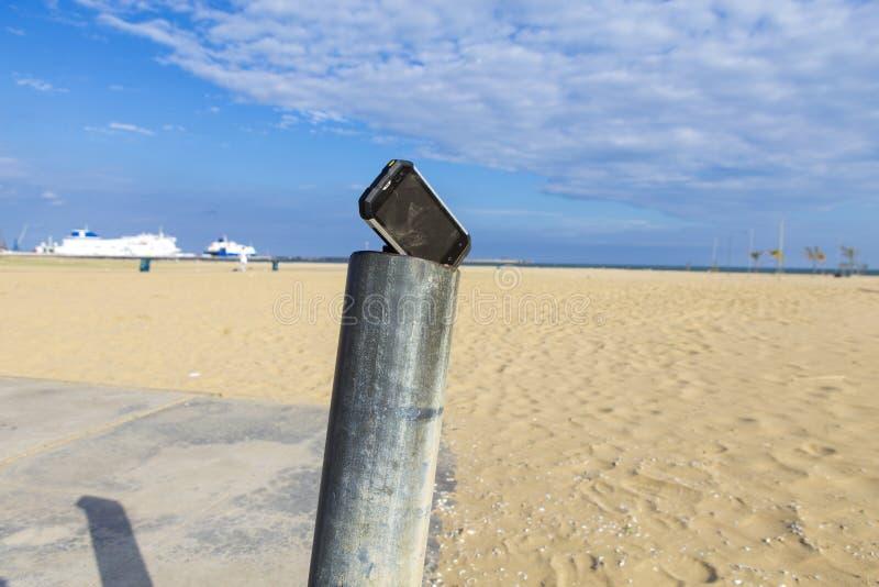 Prueba de un smartphone en arena y sol imagen de archivo