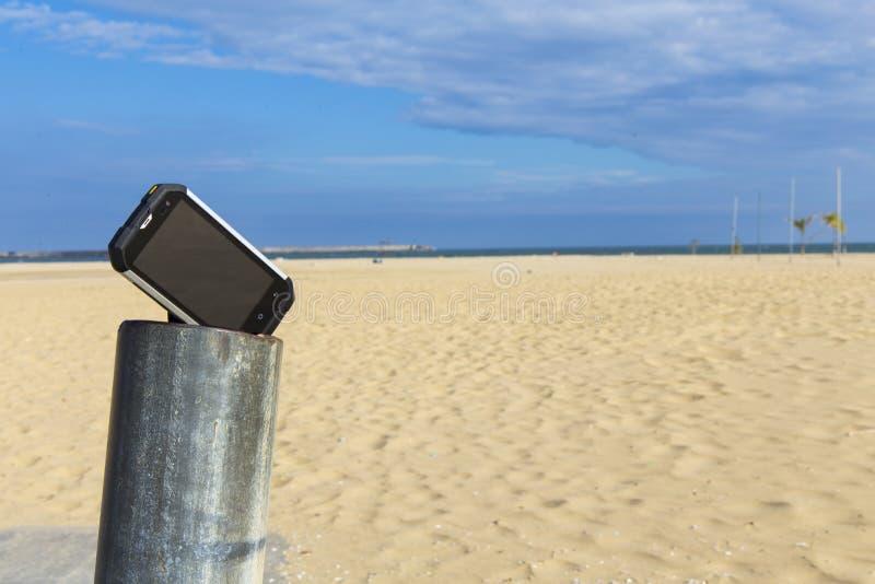 Prueba de un smartphone en arena y sol imagenes de archivo