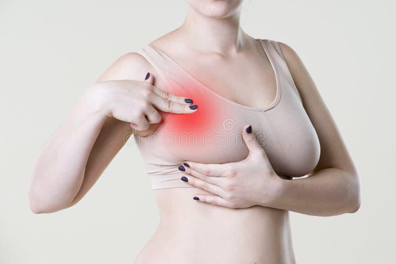 Prueba del pecho, mujer que examina sus pechos para el cáncer, ataque del corazón, dolor en cuerpo humano imagen de archivo