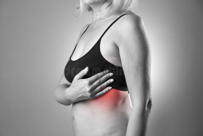 Prueba del pecho, mujer que examina sus pechos para el cáncer, ataque del corazón fotografía de archivo