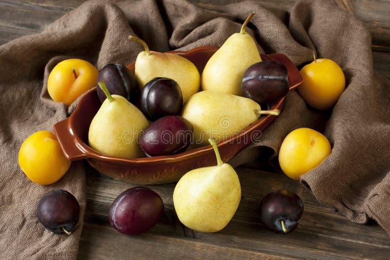 Prugne e pere fresche sulla vecchia tavola immagine stock